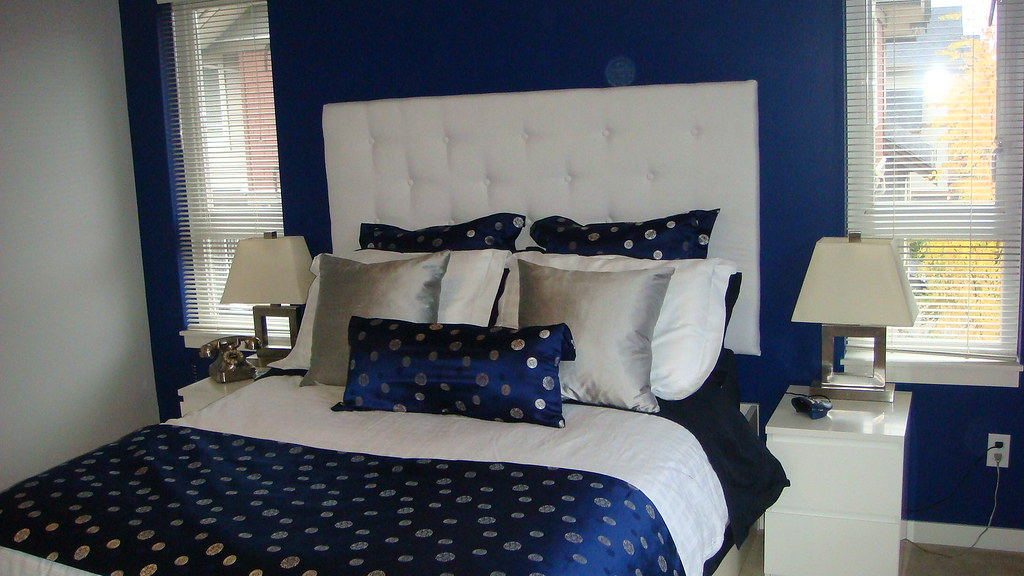 navy blue silver white bedroom with white padded headbo