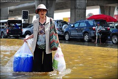 An old lady crossing the road with her belongings