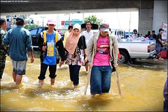 People crossing the road at flooded area