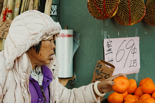 Woman Selecting an Orange, Chinatown Market in San Francisco | by CT Young