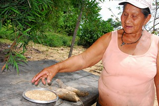 Margarita Amabeja displays the rice seed she is about to plant, and this season's first cassava. Credit: Franz Chávez/IPS | by IPS Inter Press Service