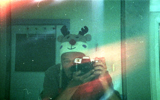 reflected self-portrait with Olympia toy camera and reindeer hat