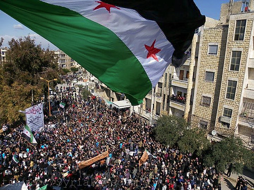 Syria independence flag flies over a large pathering of protesters in Idlib. | by FreedomHouse