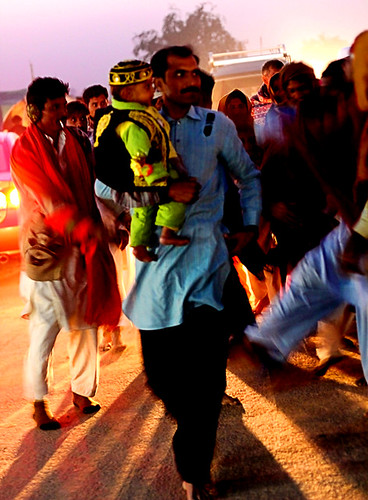 Jubilant father with son and dancing folks walk to the tomb under the vehicles lights . | by S M JOYIA