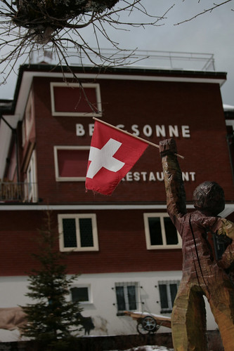 a wooden Swiss-flag-wielding statuette greets hikers along the way to Rigi Kulm | by matermorts