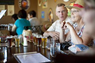 Couple laughing while enjoying a sampler at Brew Werks | by Visit Bend