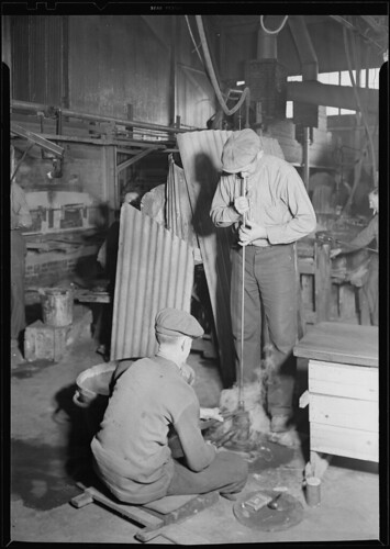 The flint glass shop showing a blower rotating a bottle as he blows it in an iron mould, March 1937 | by The U.S. National Archives