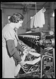 After drying, the skeins are taken from the rack and each skein is put on a swift of the winding machine. This machine winds the yarn from the skein on to bobbins, March 1937 | by The U.S. National Archives