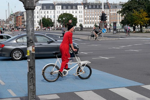Fashionable red jumpsuit woman riding a short john cargo bike | by Steven Vance