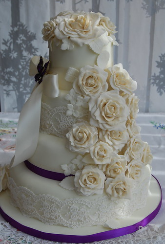 ivory wedding cake with purple roses ivory and champagne wedding cake cascading roses with cadb 16552