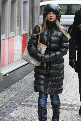 Young Blonde Girl In Black Shiny Downcoat Hood Upo And Pur