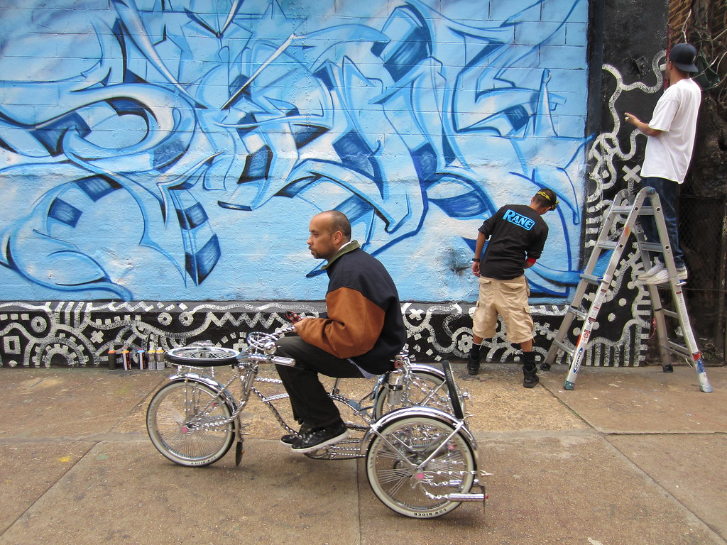 Graffiti wall in queens ny -  Customized Lowrider Bike Passing By Graffiti Artists Spray Painting A Piece On A Wall At 5pointz