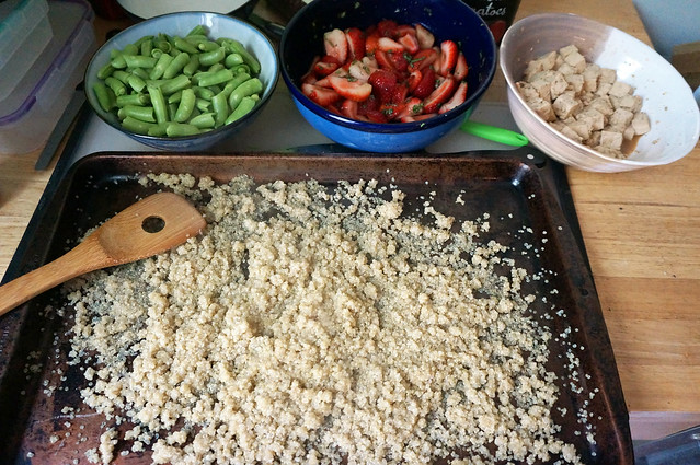 A trayful of quinoa, light tan against the dark brown, oil-stained surface of a rimmed baking sheet, sits on a countertop in front of bowl of strawberries, tofu, and sugar snap peas.