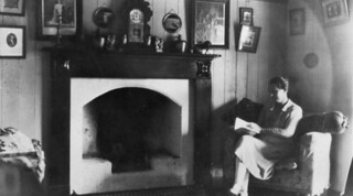 Sitting beside the fireplace reading a book, Nanango, ca. 1923 | by State Library of Queensland, Australia