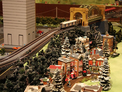 Christmas Toys Trains : Lionel train passing over a miniature christmas village on