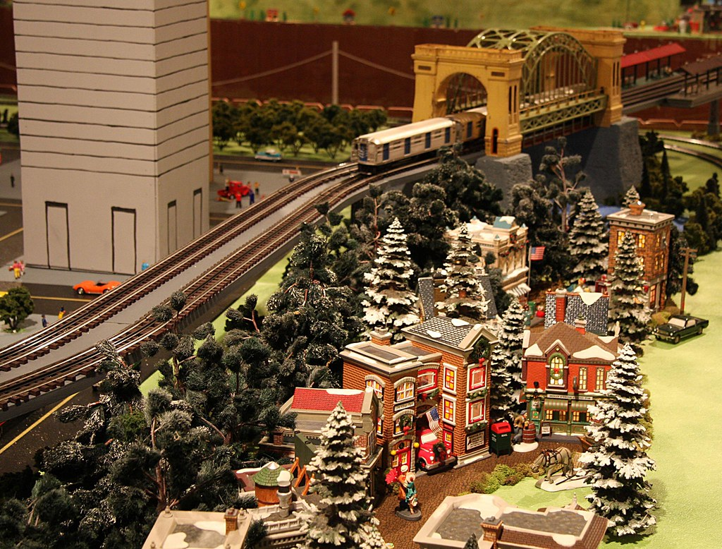 lionel train passing over a miniature christmas village on raised train tracks by the arch bridge