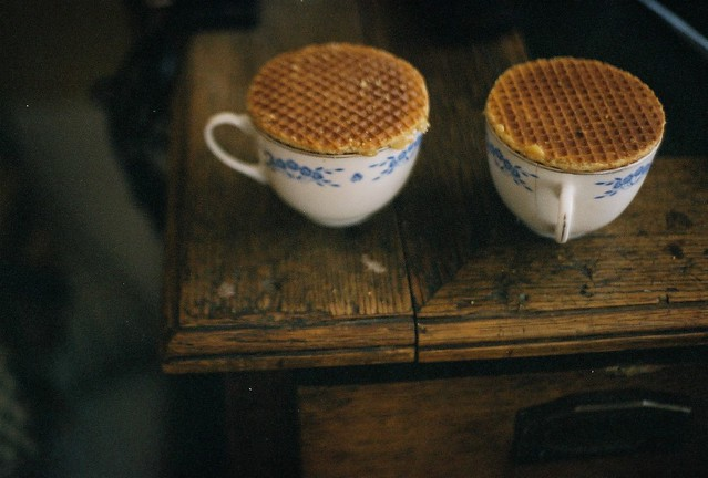 Two teacups, each with a stroopwafel on top, sitting on a table