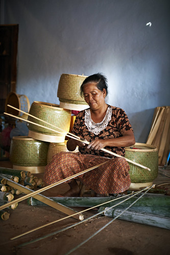 A woman cutting bamboo to weave into baskets | by World Bank Photo Collection