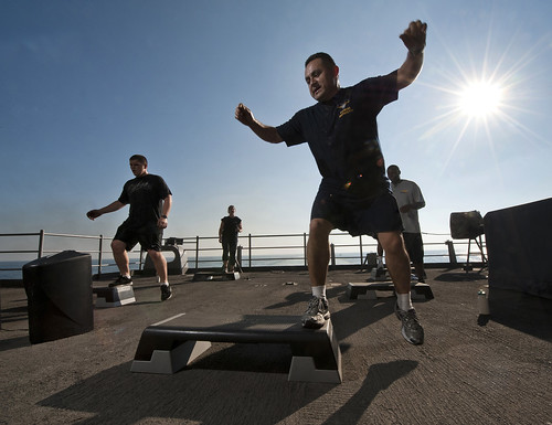 Chief Aircrew Survival Equipmentman Jose Castillo, a fitness instructor, leads a step aerobics class on the fantail of the Nimitz-class aircraft carrier USS Carl Vinson. | by Official U.S. Navy Imagery