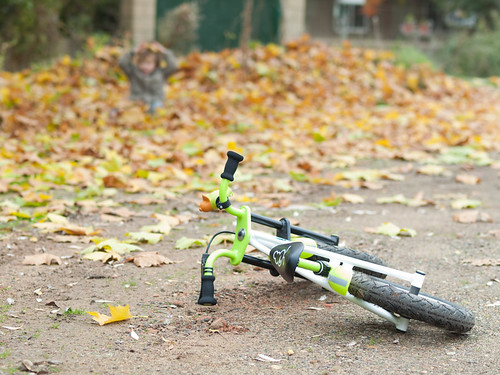 Bike on the ground and child playing with dead leaves in the background | by Carlos Ciudad - Stock Photography