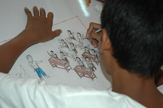 Boy drawing picture of children learning in lesson for Plan-funded drawing competition | by Plan Asia