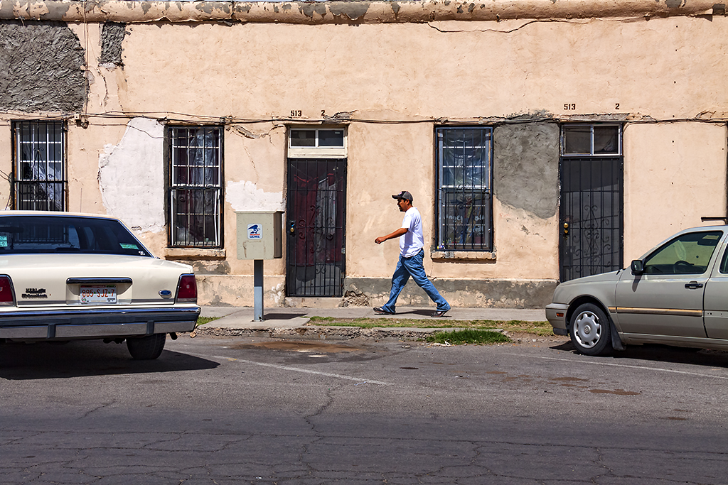 Man walking by plain houses--El-Paso
