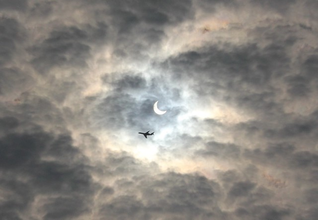 An image of an eclipse obscured by clouds. A plane is flying just beneath it.