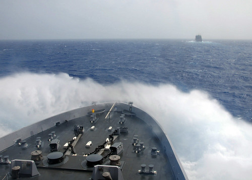 Waves break over the bow of USS New York. | by Official U.S. Navy Imagery