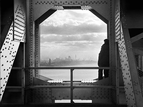A workman taking a break between the bolts and beams of the George Washington Bridge facing  the smoky skyline of 1930s Midtown Manhattan.  1936 | by wavz13