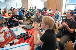 Attendees clap in the Hacker Lounge at the closing ceremonies | by Igal Koshevoy