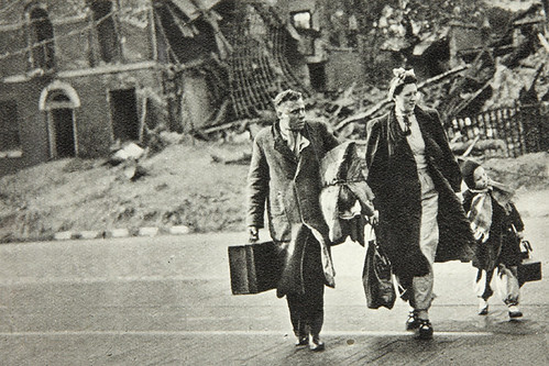 Bombed out family cross the road with their belongings | by The National Archives UK