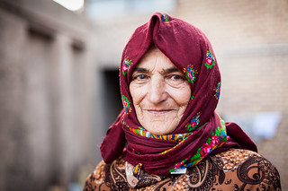 Older woman with red hijab standing in her home's courtyard | by damonlynch