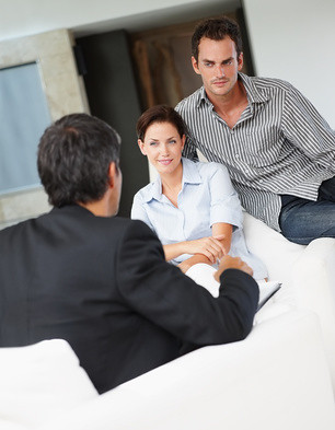 Happy young couple in discussion with a financial advisor | by SalFalko