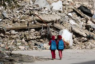 Syrian girls, carrying school bags provided by UNICEF, walk past the rubble of destroyed buildings on their way home from school on March 7 in al-Shaar neighborhood, in the rebel-held side of the northern Syrian city of Aleppo. (IZEIN ALRIFAI/AFP/GImages) | by Jordi Bernabeu