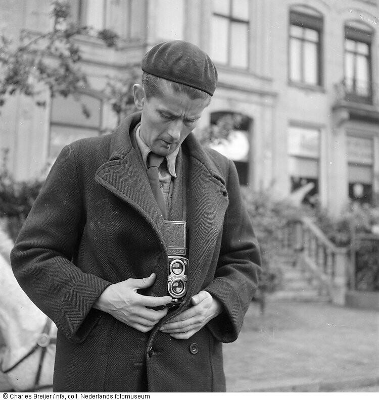 Cas Oorthuys con una cámara oculta bajo su abrigo (grabación reconstruida después de la guerra ), en su casa en el Amstel 3, Amsterdam (finales de mayo de 1945). Foto de Charles Breijer.