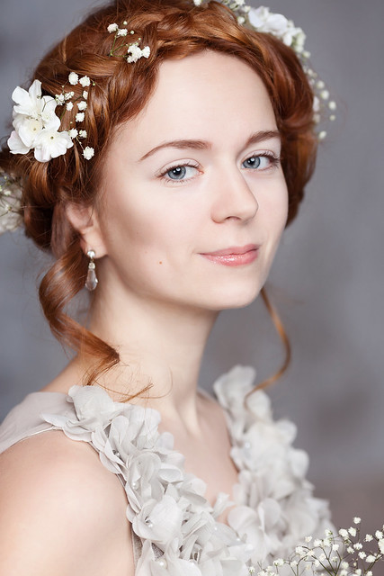 Portrait of beautiful red-haired bride. She has a perfect pale skin with delicate blush. White flowers in her hair. She smiles gently. She has light gray eyes.