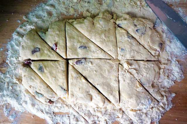 A rectangle of scone dough on a floured wooden surface. The dough, studded with little bits of rhubarb, has just been cut into twelve neat triangles.
