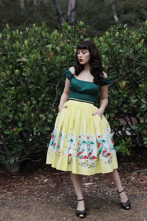 Pinup Girl Clothing Pinup Couture Peasant Top in Dark Green Jenny Skirt in Mary Blair Yellow Umbrellas Print