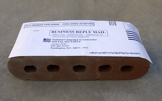 Pre-paid envelope taped to a brick | by Judith E. Bell