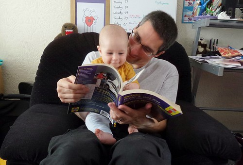 a man with a baby on his lap, both smiling, reading a Haynes manual