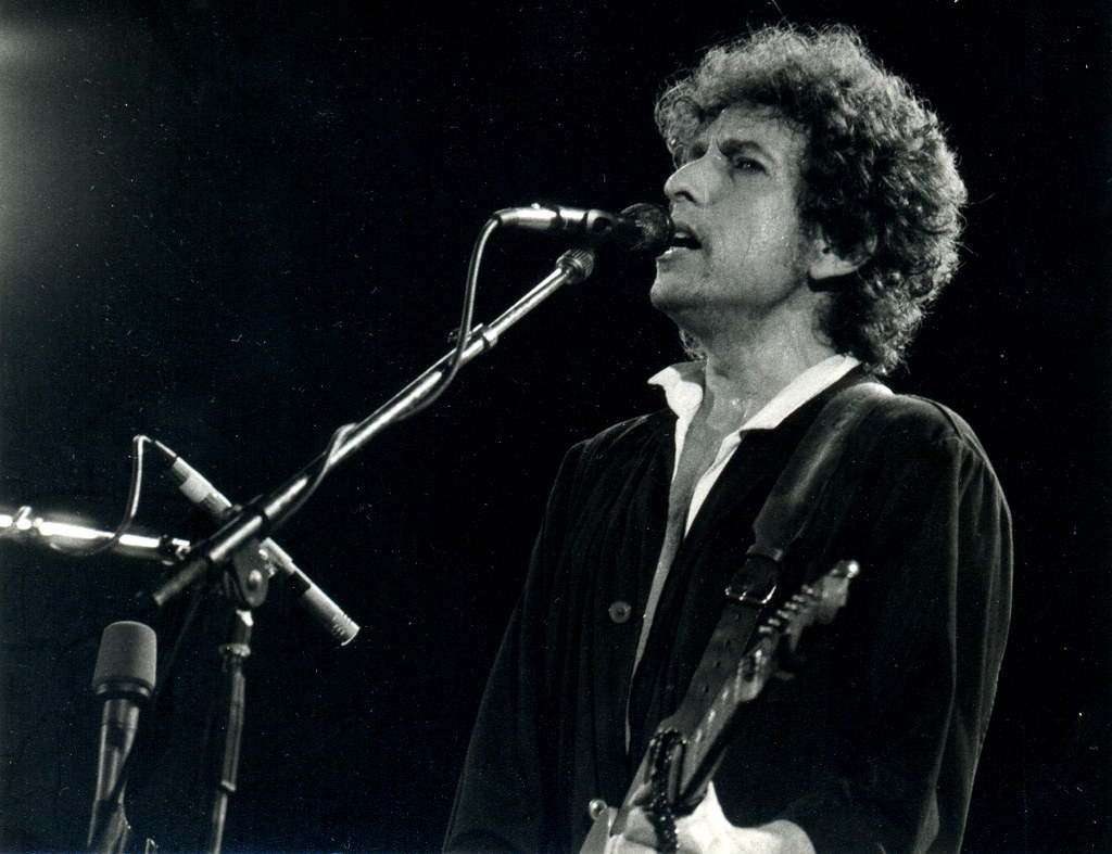Picture of Bob Dylan singing and playing guitar