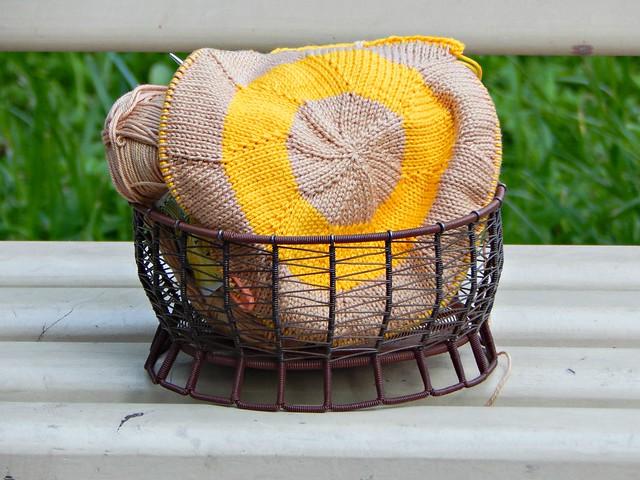жёлтая и бежевая хлопковая пряжа в плетёной клубочнице, почти законченная прихватка, которую я вяжу на спицах | ХорошоГромко.ру
