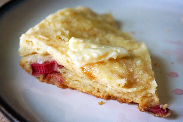 Closeup on a split half of a rhubarb buttermilk scone, butter melting down onto its flaky layers studded with pieces of bright-red rhubarb.