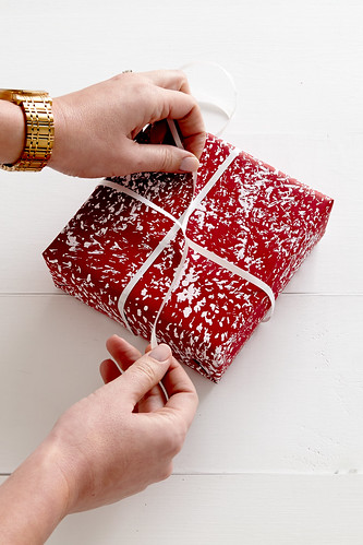 A woman's hands tying a ribbon around a red gift wrapped present with fake snow paint on a white table | by ProFlowers.com
