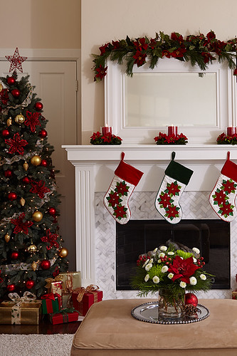 Poinsettia flower centierpieces with candles on mantel ove ...
