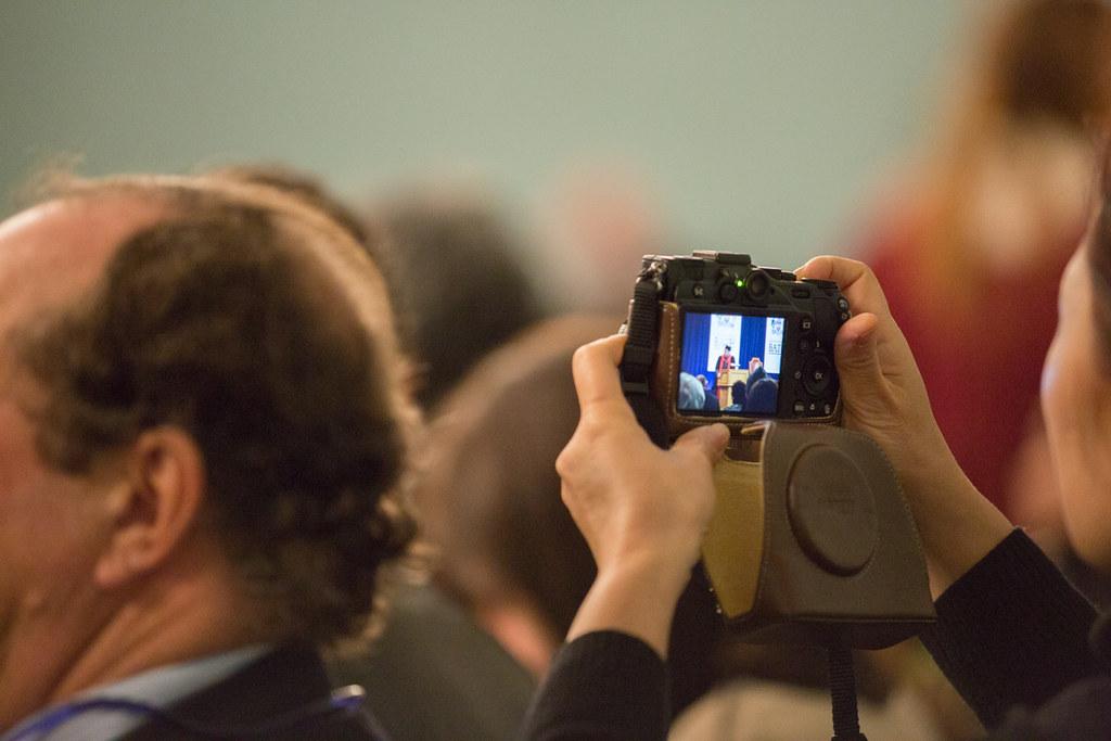 A parent filming a video at graduation