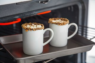 two mugs of hot cocoa on a tray in the oven | by PersonalCreations.com