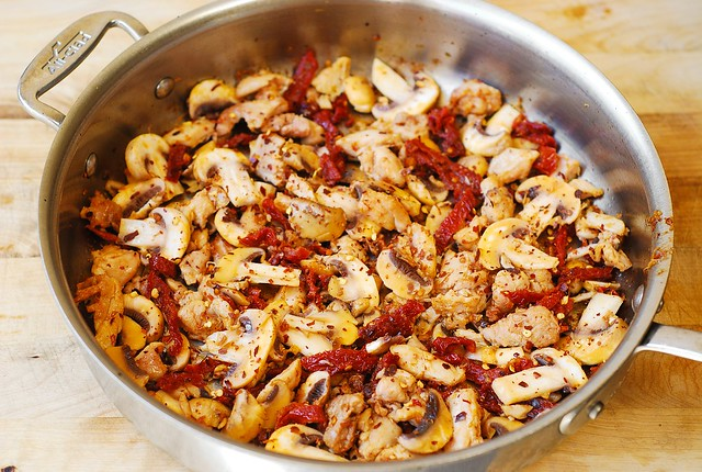 chicken, sun-dried tomatoes, mushrooms with olive oil in a skillet