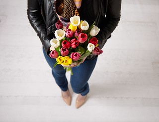 woman in leather jacket with bouquet of assorted multi-colored tulips | by ProFlowers.com