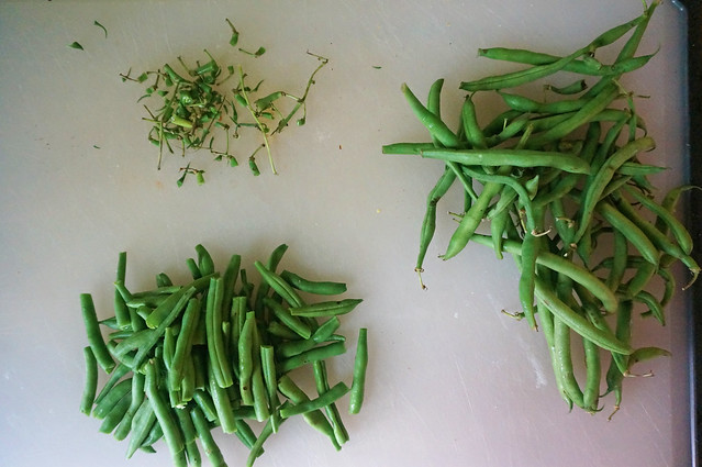 Green beans, semi-deconstructed: three piles on a cutting board. A large, unruly pile of unprocessed beans sits to the right, while on the left are two smaller piles of trimmed stems and beans snapped down to size and neatly stacked.